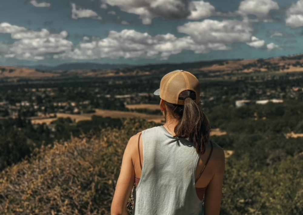 image of back of woman looking out over valley