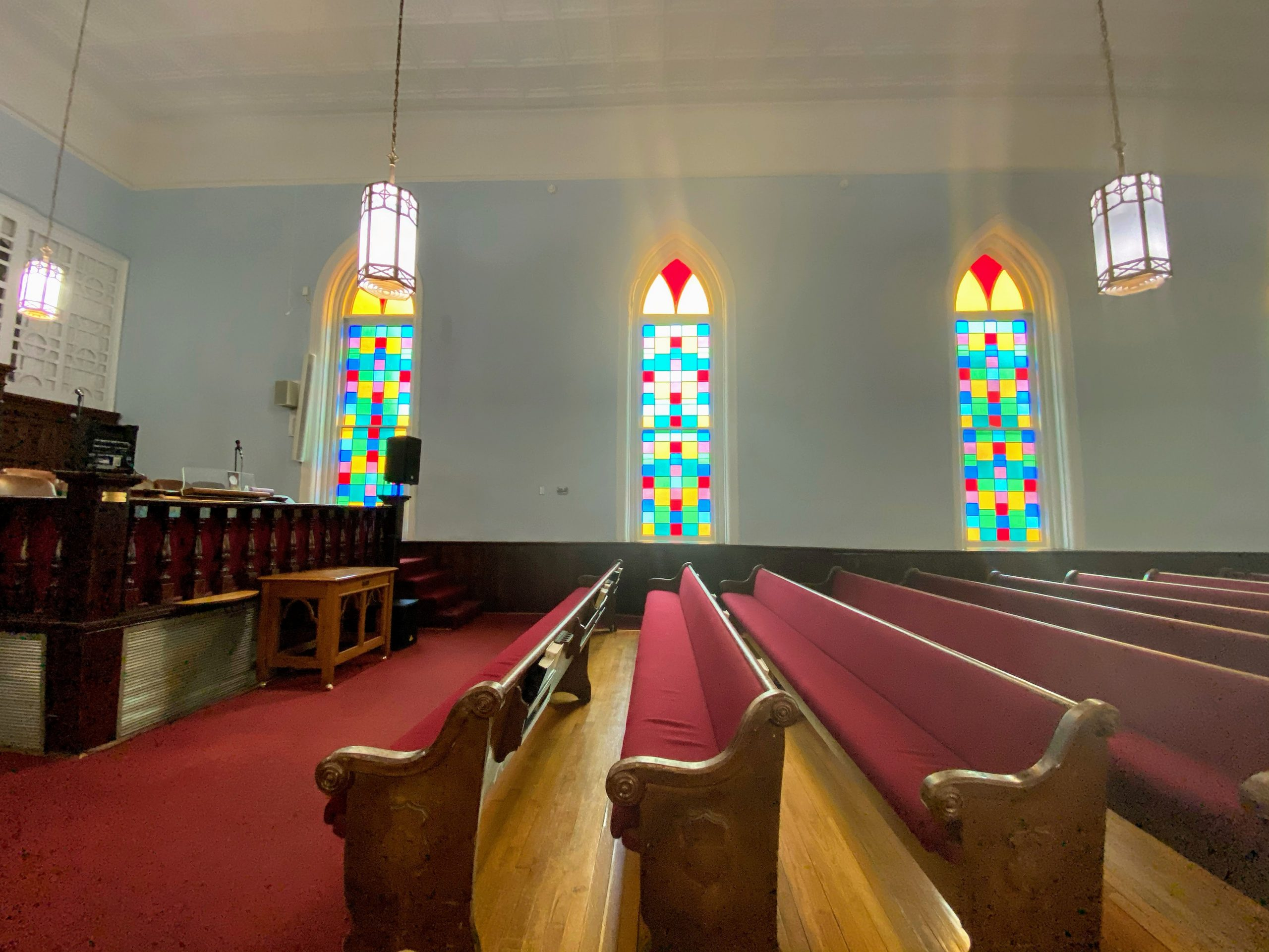 church pews with stained glass in background